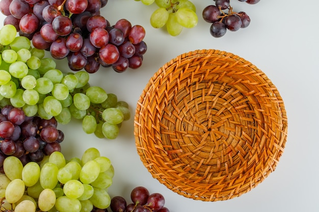 Ripe grapes with empty basket flat lay on a white
