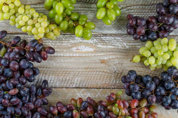 Ripe grapes on wooden background, flat lay.