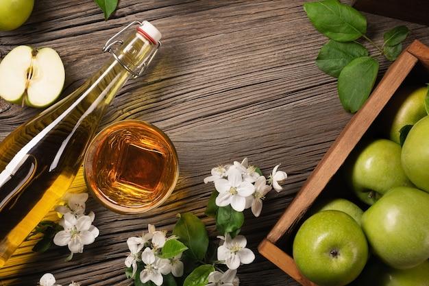 白い花の枝、ガラス、木製のテーブルにサイダーのボトルと木製の箱に熟した緑と赤のリンゴ。テキスト用のスペースがある上面図。