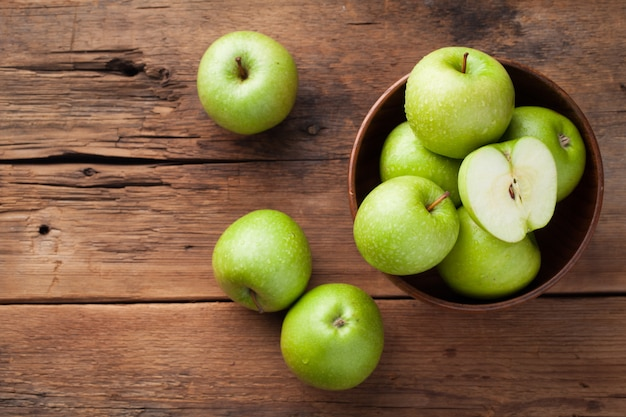 나무 그릇에 익은 녹색 사과.