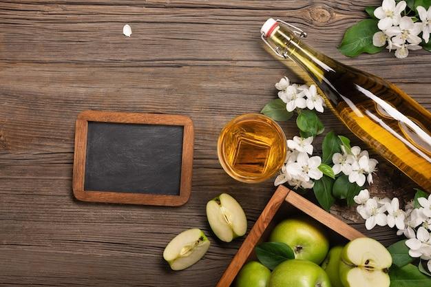 白い花の枝、ガラス、フレッシュジュースのボトル、木製のテーブルにチョークボードと木製の箱に熟した青リンゴ。テキスト用のスペースがある上面図。