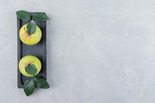 검은 접시에 익은 녹색 사과.