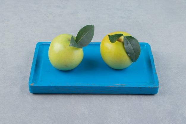 Спелые зеленые яблоки на голубой тарелке.