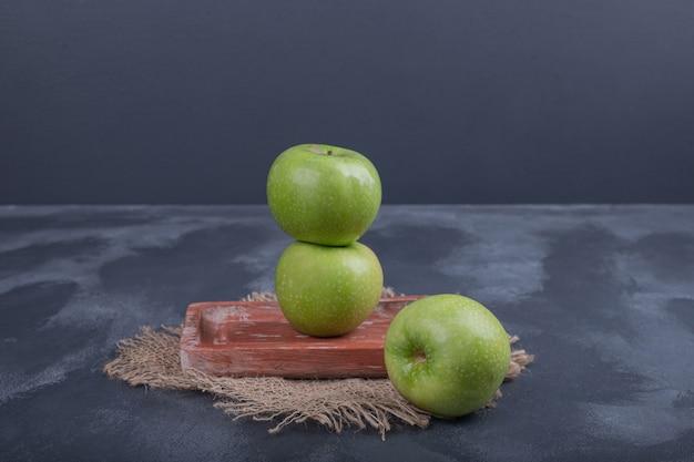 Спелые зеленые яблоки на синем столе.