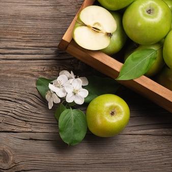 나무 테이블에 나무 상자에 흰색 꽃의 분기와 익은 녹색 사과. 텍스트를 위한 공간이 있는 상위 뷰입니다.