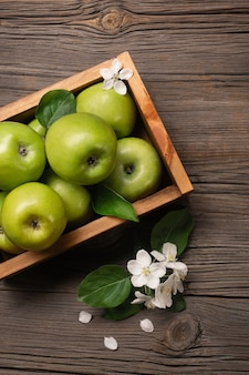 Ripe green apples with branch of white flowers in wooden box on a wooden table. top view.