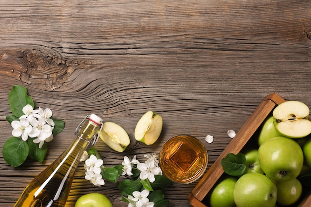 Ripe green apples in wooden box with branch of white flowers, glass and bottle of cider on a wooden table. top view with space for your text.