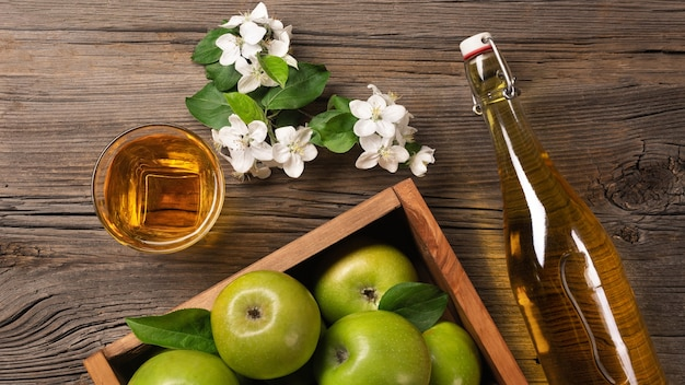 Ripe green apples in wooden box with branch of white flowers, glass and bottle of cider on a wooden table. top view.