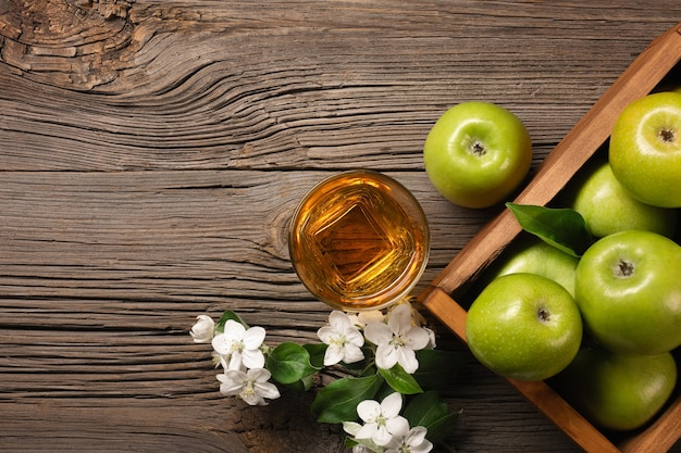 Ripe green apples in wooden box with branch of white flowers and glass of fresh juice on a wooden table. top view with space for your text.