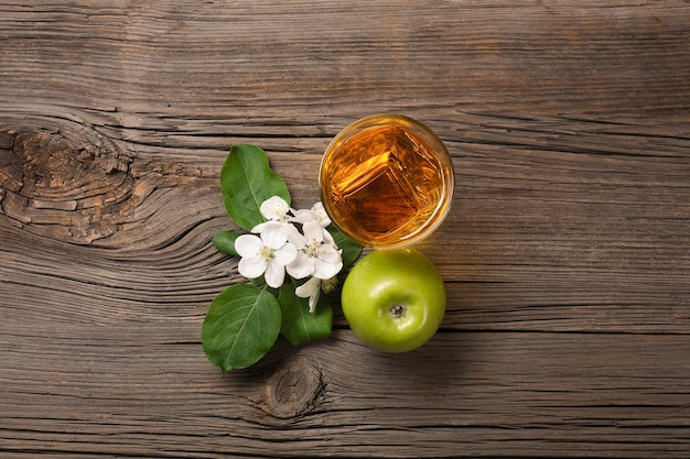 Ripe green apples in wooden box with branch of white flowers and glass of fresh juice on a wooden table. top view.