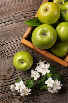 Ripe green apples in wooden box with branch of white flowers on a wooden table. top view.