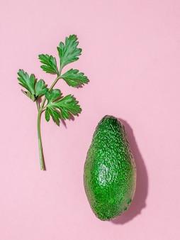 분홍색 배경에 파슬리 장식이 있는 익은 녹색 아보카도. 맛있는 열대 야채. 플랫 레이.