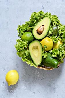 青灰色の背景のバスケットにレモンとレタスと熟した緑のアボカド