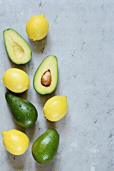 ブルーグレーの背景にレモンと熟した緑のアボカド