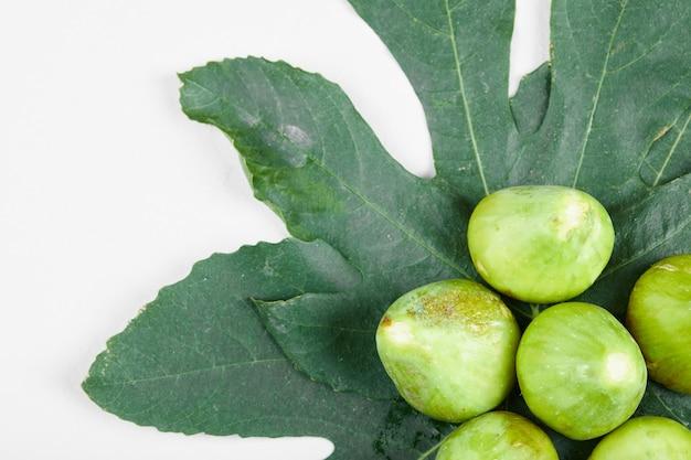 Fichi verdi maturi sulle foglie. avvicinamento. foto di alta qualità