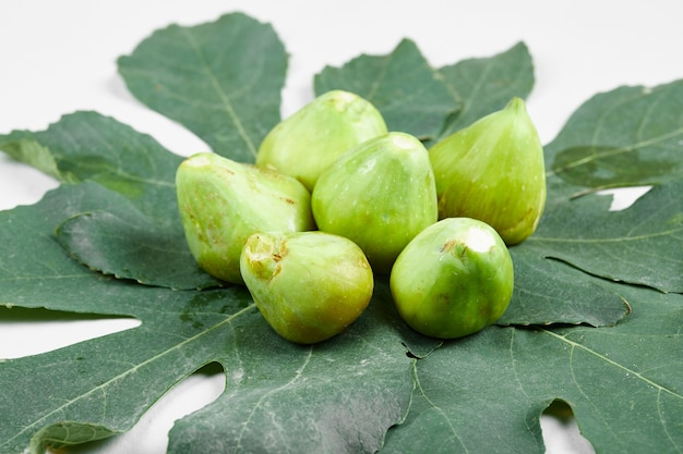 Fichi verdi maturi con foglie su sfondo bianco. foto di alta qualità