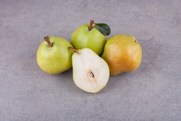 Ripe green pears with leaves placed on a stone surface .