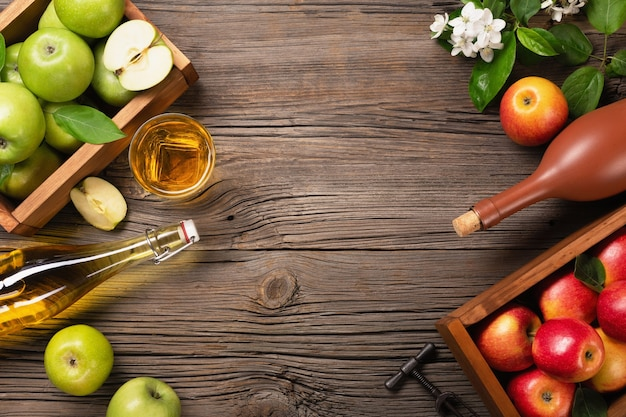 Ripe green and red apples in wooden box with branch of white flowers, glass and bottle of cider on a wooden table. top view with space for your text.