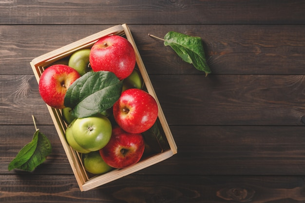 Ripe green and red apples in a wooden box with leaves on dark brown wooden rustic.