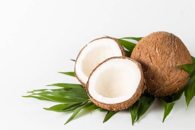 잘 익은 절반 나무 배경에 코코넛을 잘라. 코코넛 크림과 오일.