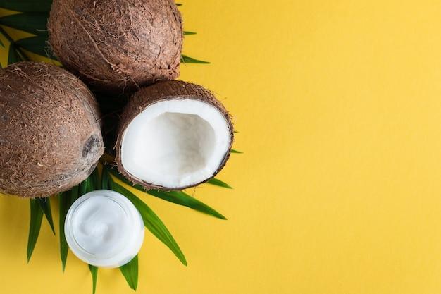 熟した半分は黄色の背景にクリームと緑の葉とココナッツをカット