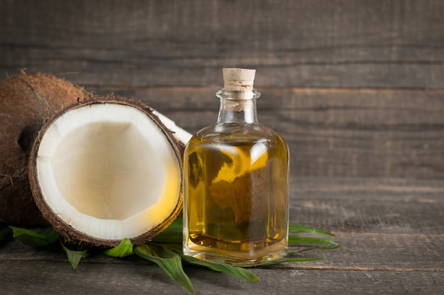 Ripe half cut coconut with green leaves on a wooden background