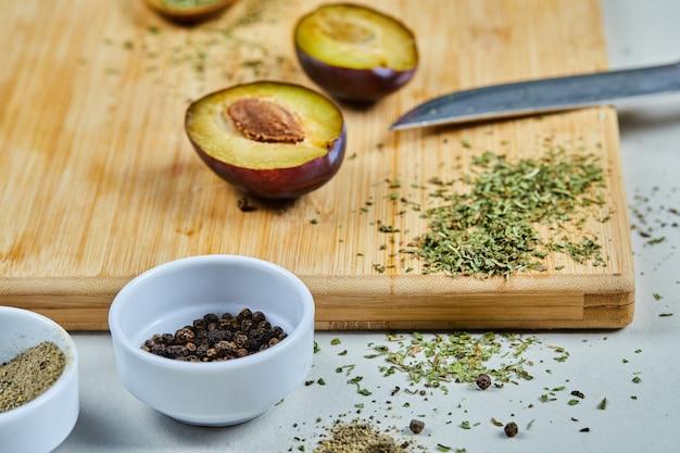 Mezzo taglio maturo di prugna su tavola di legno con spezie.
