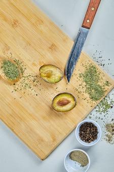 Taglio a metà maturo di prugna su una tavola di legno con spezie