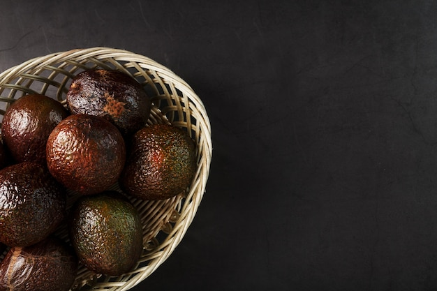 Ripe hass avocado in a basket on a black textured surface