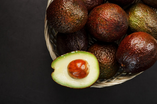 Ripe hass avocado and a pitted slice in a basket on a black textured surface
