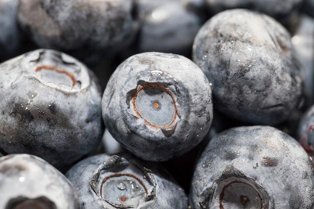 熟したジューシーでおいしいブルーベリーを木製のテーブルに大量に置き、ブルーベリーは季節に収穫されます