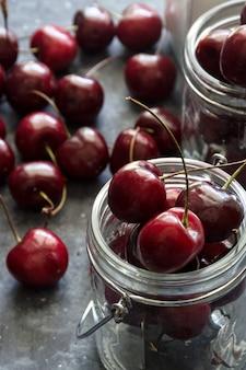 Ripe and juicy cherries on table in jars, dark background.