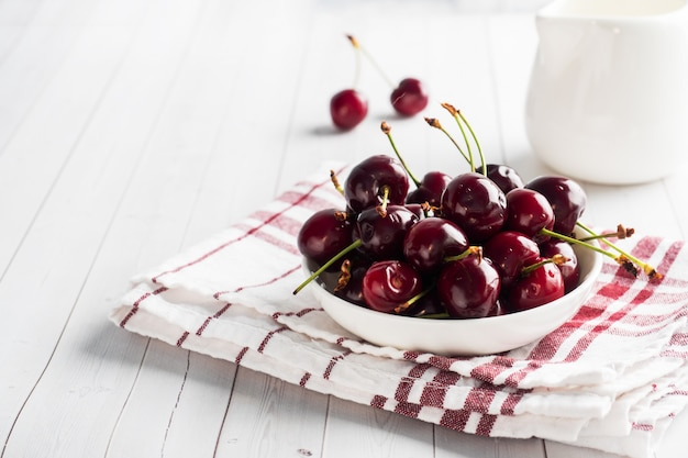 Ripe juicy cherry berries on a plate. white background. .