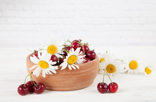 Ripe juicy cherry berries on a white wooden background