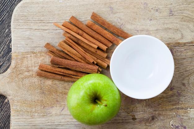 木製のまな板に熟したジューシーなグリーンアップルと香りのよいシナモン、有機農場で栽培された自然生産の食品のクローズアップ