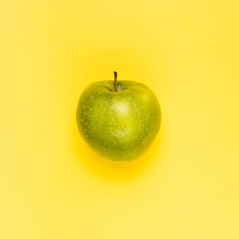Ripe juicy green apple on yellow surface