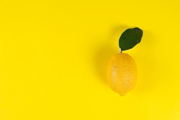 色付きの黄色の背景の葉と熟したジューシーなレモン