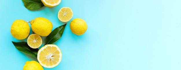 Спелые сочные лимоны и зеленые листья на ярко-синем фоне. лимонный фрукт, минималистичная концепция цитрусовых, витамин с. креативная летняя еда минималистичный фон. плоская планировка, вид сверху, копия пространства, баннер
