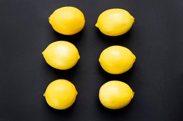 黒の背景に熟したジューシーなレモンレモンフルーツ柑橘類の最小限の概念ビタミンcクリエイティブなミニマルな背景