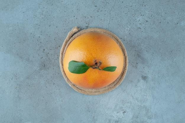 Спелый сочный апельсин на подставке, на мраморном фоне. фото высокого качества