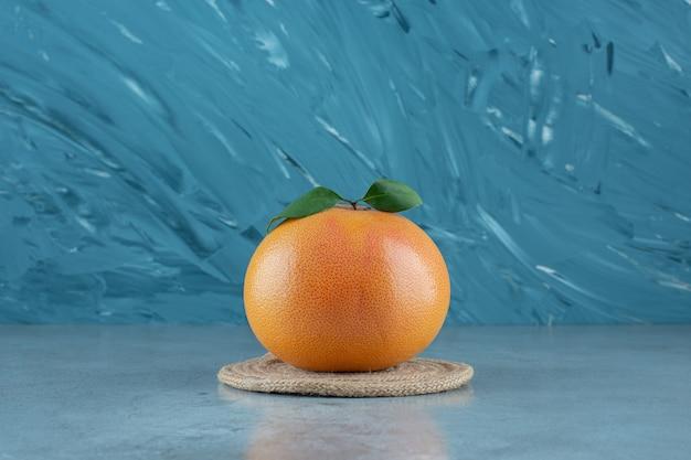 Arancia succosa matura su un sottopentola, sullo sfondo di marmo.