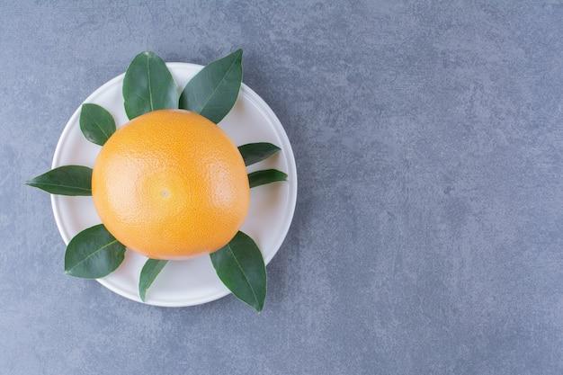 Спелый сочный апельсин с листьями на тарелке на мраморном столе.