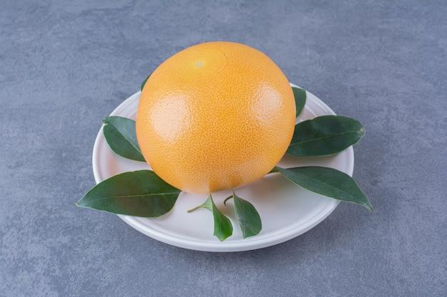 Спелый сочный апельсин с листьями на тарелке на темной поверхности
