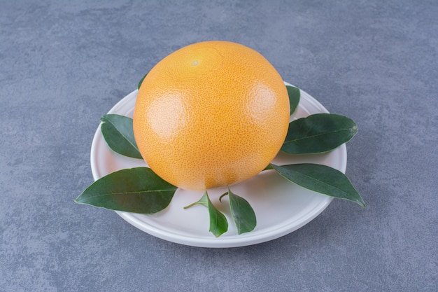 Ripe juicy orange with leaves on plate on the dark surface