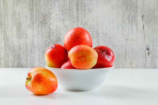 Ripe juicy peaches in a white bowl on grungy wall and white surface, side view.