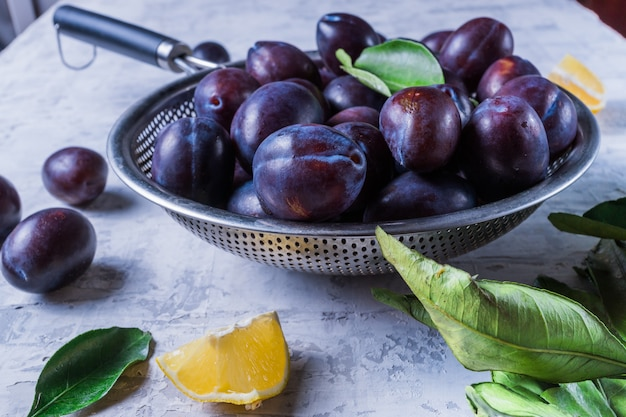 Ripe juicy plums on a colander, on old white wooden table.