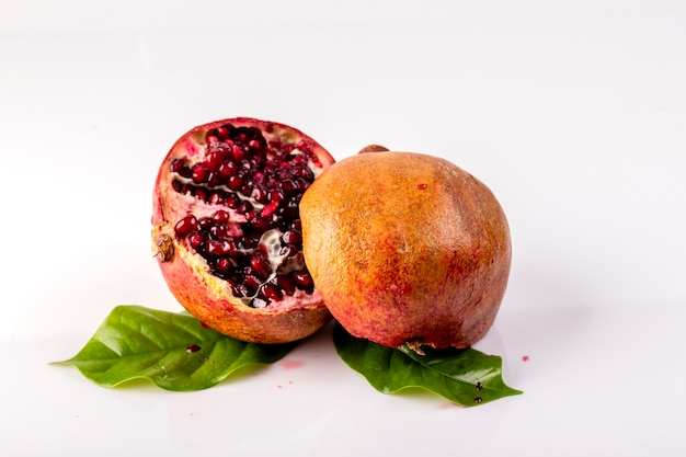 Ripe and juicy pomegranate is cut into two parts with leaves on a white background.