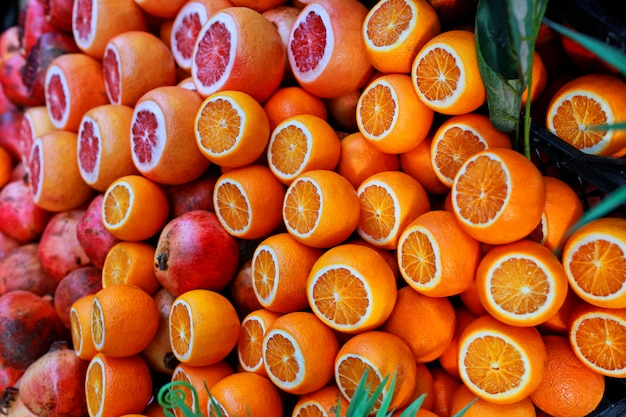 Ripe juicy pomegranates, tangerines and oranges are sold on the counter of a fruit shop on istanbul street.