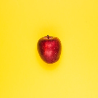 Ripe juicy red apple on yellow surface