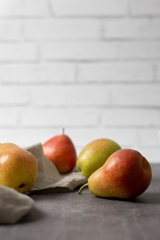 Ripe juicy red yellow pears on a gray concrete background and brick wall.